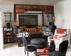 In a guest bedroom, an antique opium bed from Bali is dressed with an African quilt and pillows covered in ikat prints and Balinese sarong fabrics; the armchair is by Bergamin, the ottoman and rugs are African, and the shelf holds books covered in  a Ralph Lauren Home fabric.    - ELLEDecor.com