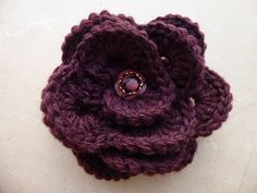 """Crocheted flower brooch made of soft yarn, pin flower was embellished with hand vintage button. This beautiful blossom pin will make every outfit look fabulous. Perfect accessory for upcoming fall/winter season. A beautiful addition to any wardrobe, on coats, hats, sweaters, bags, purses or shawls. Colors: wine colour, plum color. It has a pin sewed at the back. Dimension: 13 cm – 5"""" inches. It also makes a lovely gift. More flower pins: https://www.etsy.com/it/sh..."""