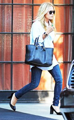 Mary-Kate Olsen wears a pale blue button-down blouse, skinny jeans, a black tote, aviator sunglasses, cocktail rings, a bold watch, and black pumps