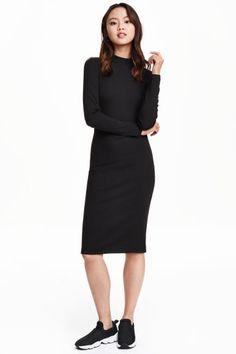 Geribde jurk: Een knielange, getailleerde jurk van ribtricot met lange mouwen en een opstaand halsboordje.