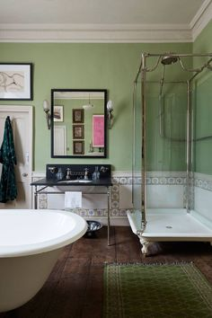 The spacious guest bathroom has muted, sea green walls.