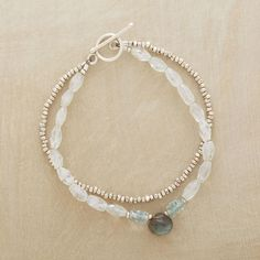Double strands combine luminous moonstones with the liquid light of tiny apatite rondelles, accented with a labradorite briolette and sterling silver...