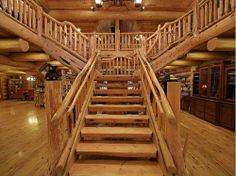 """Massive rustic staircase all natural wood, """"branching"""" out both directions. Matching wood floors."""