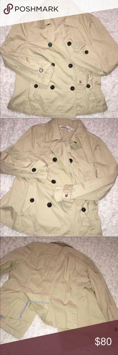 """Tommy Hilfiger Short Cotton Trench Coat EUC. Ladies or Junior's. Tan/Nude/Beige. Trench jacket coat. Brown buttons. Denim like feel, all cotton. Buttons either way..left over right side, or right over left side..buttons and holes to accommodate either. Slanted pocket at either side. Slits at back for feminine flare.   100% cotton   Size Large (G/G) 19"""" armpit to armpit laying flat  24"""" length from shoulders  16"""" across the shoulders from seam to seam  15.5"""" sleeve inseam  22"""" sleeve length…"""