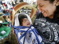Michelle Richardson shares a giggle with her two-month-old son, Michael, who is in a hand-made cedar cradle board.  The cradle board, she explained, is traditionally made by the males in the family.  In this case, little Michael's father and grandfather made the cradle board. Richardson is with the Haliwa-Saponi Native American Indian tribe in Hollister, North Carolina.