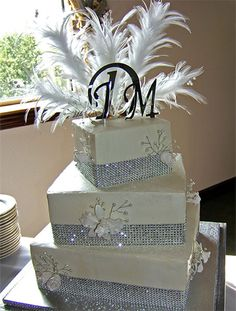 white 3-tiered square wedding cake with frosted flowers, feather on top layer and rhinestone trim on each layer