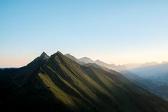 A sloping mountain range with pointy peaks under a blue sky, with soft sunlight