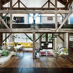 Spacious living room, with open stairway up to a loft.I like the natural lighting and modern appeal to what might be a rustic house on the outside.