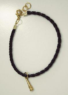 Pulseira que representa o orixá Omolu ou Obaluaê, seu pingente é o xaxará (ferramenta usada pelo orixá). <br>Tenho nas cores prata ou dourado e cordão preto ou cru.