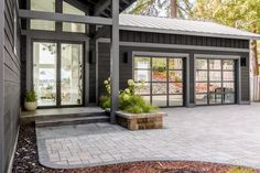 A new exterior painted black with updated driveway and landscaping creates a bold front yard that sets the tone for HGTV Dream Home a moody modern escape with a coastal twist. Garage Windows, Glass Garage Door, Garage Doors, Garage Pictures, Room Pictures, Kitchen Pictures, Hgtv Dream Homes, Waterfront Homes, Cabin Homes