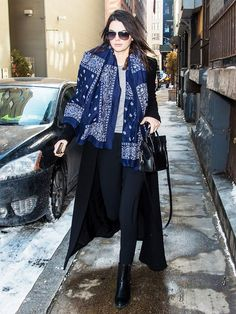 Kendall Jenner in an oversized paisley-print scarf and tall leather boots.