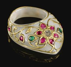 A GEM-SET JADE ARCHER'S RING, INDIA, CIRCA 1800 the pale grey jade of typical form inlaid with foliate gold tendrils issuing kundan-set buds and flowerheads of emerald and ruby encircling a central cut-diamond 4.5cm.