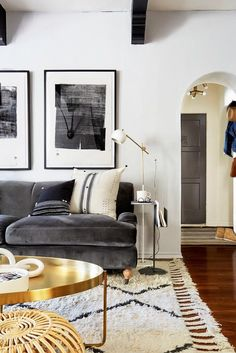 Living space with a gray velvet English roll-arm sofa, black and white art, a simple side lamp, and wool rug