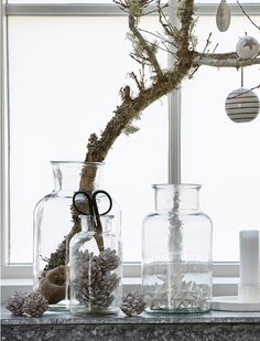 lichen-covered branch w/ ornaments in a vase