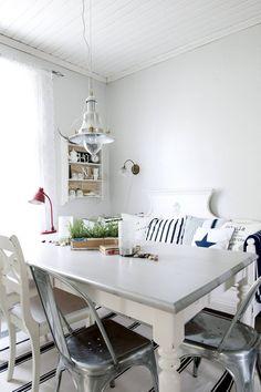 Suuri puinen ruokapöytä sekä vanha puusohva ovat löytöjä netti-huutokaupasta. Puutuolit ovat löytyneet talon ulkorakennuksesta ja metallituolit ostettu ulkomaalaisesta nettihuutokaupasta. Valaisin Ellokselta.