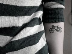 Small bicycle tattoo on forearm.