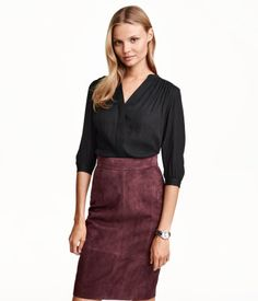 Wide-cut, V-neck blouse in woven fabric with a slight sheen. Concealed buttons at front, contrasting satin yoke, and 3/4-length sleeves with buttons at cuffs. Short slits at sides. Slightly longer at back.