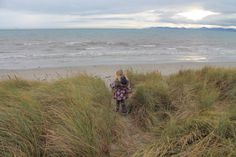 Playing in the long grass on Dollymount Beach with views of Dublin Bay.
