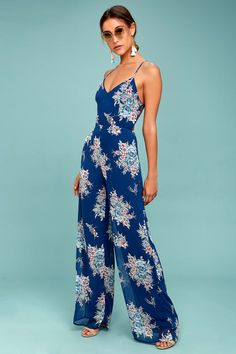 The Shea Navy Blue Floral Print Jumpsuit is a flirty addition to any wardrobe! Lightweight chiffon, in a navy blue, light blue, sage green, and rust red floral print, falls from crisscrossing spaghetti straps, (that lace-up at back) into a princess-seamed bodice. Fitted waist tops breezy wide-leg pants. Elastic at back for fit, and hidden zipper/clasp.