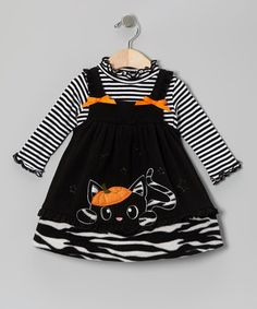 Sweet, bashful little kitty scampers under a pumpkin on a black licorice colored jumper and striped top.  Available early fall.