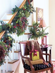 Put wreaths on display beyond the front door. Here, they form an exuberant showcase of evergreens and berries on a stairway.