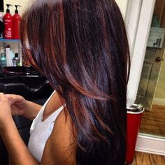 Dark burgundy hair with dark brown on the tips and sides with long cut layers.