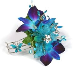 http://www.goedkoop-bloemschikken.nl/luxe-bruidsdecoratie-oa-polscorsage/1710916-corsage-polscorsage-armband-alpine-meadow.html Prom corsage of dyed dendrobium with teal accents
