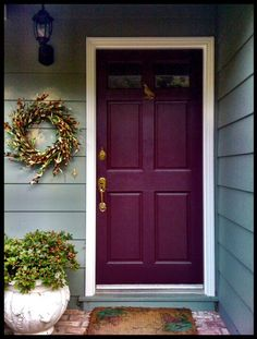 Door painted a different color and wreath beside it.