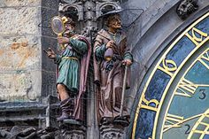 Statues on Prague Astronomical Clock, 1410. Vanity admires himself in a mirror, while the miser holds a bag of gold, representing greed or usury.
