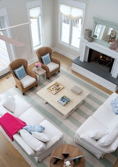 source: Erica Burns Interiors  Open, airy living room with fireplace as focal point of space. Sand paint color, pair of wicker accent chairs, ivory & celadon green awning stripe rug, white slipcover sofas, ivory roman shades covering windows, trestle cocktail table and blue pillows.