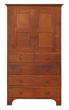 Cupboard Over Drawers - Pine, old refinish, remnants of original yellow and red stained finish, applied cove molded top, two vertical double inset panel doors with applied molding, through mortise construction, original hardwood pulls with mortise and pinned Shaker door closures, three-shelf interior, over two flanking dovetailed drawers over three full dovetailed drawers on a cut out base, arched sides, c. 1820-1830, 78″ h, 42″ w, 19″ d.