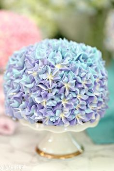 These Hydrangea Cakes are gorgeous miniature cakes that look like hydrangea flowers! You'll be surprised to learn how easy it is to make the pretty, colorful blossom design on the outside. The inside is beautiful, too, with swirls of multicolored cake! | From SugarHero.com #sugarhero #hydrangea #minicakes #spring