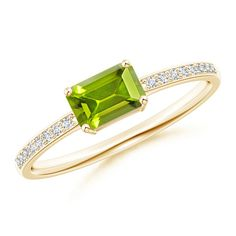 In the middle of a sleek diamond encrusted band is an emerald cut peridot mounted horizontally. East West Emerald Cut Peridot Solitaire Ring with Pave Diamonds.