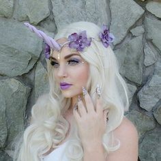 This is a gorgeous silver and lavender unicorn headpiece. Silver plated chains hang on each side with lavender flower accents, tiny lavender teardrop crystals and one larger teardrop pendant in the center. The horn is made from polymer clay and is wire wrapped to the headpiece. It ties in the back with organza ribbon for an adjustable fit.