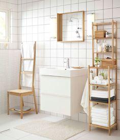 화이트 세면대와 수건걸이의자, 대나무 소재의 선반유닛과 거울이 있는 욕실