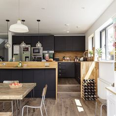 We love it when homeowners go bold with their kitchen design. These matt black units look perfect against the slim wooden worktops . Photo: Simon Maxwell . #home #kitchen #kitchendesign #pendentlights #modern #myhomevibes #bold #dark #blackkitchen #contemporary #scandi #extension #dramaticdesign #interior #livingroom #kitchendiner #ideas