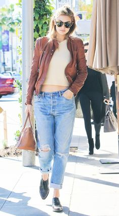 Gigi Hadid wears a neutral cropped sweater, brown leather jacket, boyfriend jeans, and oxfords