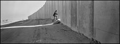 Larry Towell - Jerusalem. 2004. A Palestinian man runs through an opening in the wall