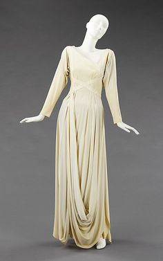 Valentina, a prominent New York designer, often used jersey in evening gowns that she effortlessly shaped using inventive construction and drapery techniques. This example, worn by style arbiter Millicent Rogers and influenced by ancient Greek dress, exhibits Valentina's talent for creating minimalist, yet modern, designs, particularly illustrated in the tucks on the bodice which flow into elegant draped loops