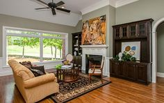 Designer Builders - Aiken SC - wood fireplace surround, entertainment built in, sage green walls, traditional living
