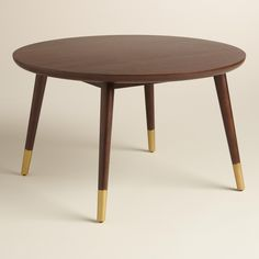 Our round coffee table features splayed legs with gold-painted tips for a mid-century aesthetic and a tabletop with a beveled edge for added interest. Use alone or nest it with our Small Wood Randon Coffee Table for an elevated look.