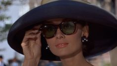Audrey Hepburn wears a wide-brimmed hat and oversized sunglasses in 'Breakfast at Tiffany's'