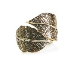 "ERES GOLD  Just in time for Fall, the matte gold Eres cuff features bold, chunky leaves with intricate etched veins. Eres will take you from workday to girls night out with style.  - Gold plated base metal, enamel  - Hinge opening  - Fits 6- 8.5"" wrist comfortably"
