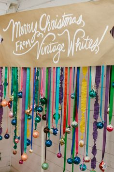 (photo booth) brightly colored ribbon and ornaments on a PVC frame to create a super fun and festive backdrop, and scattered neon pom-poms all over a tree…