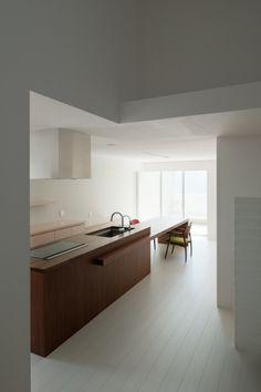 cocina con isla central para fregadero, zona de cocción y barra, muebles bajos color claro, paredes y suelo de parquet pintado color blanco