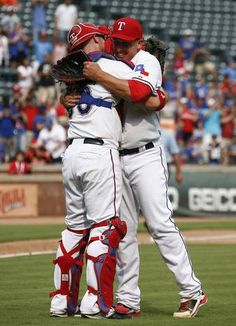 Aug 30, 2015; Arlington, TX, USA; Texas Rangers starting pitcher Derek Holland (right) celebrates his complete game three-hit shutout with catcher Chris Gimenez (38) against the Baltimore Orioles following a ballgame at Globe Life Park in Arlington. The Rangers won 6-0. Mandatory Credit: Jim Cowsert-USA TODAY Sports