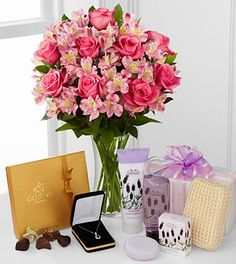 """Gratitude Ultimate Gift is an expression of timeless elegance and grace... bouquet of 9 pink roses accented with 11 pink Peruvian Lilies with a clear glass vase, a 19-piece box of Godiva® Chocolates, a 1-5/8"""" genuine amethyst pear drop sterling silver pendant, and a spa set in the scent of soothing lavender. Arriving in one large gift box, this ultimate gift is filled with a sweet sophistication to honor your special recipient."""