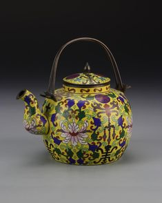Chinese Cloisonne Teapot ROC period, cloisonne teapot, with bulbous body, curved spout, and double ring metal handle, the body decorated with large colorful flowers and auspicious symbols against a yellow ground, mark on base. Height 5 in., Width 6 1/2 in.