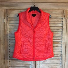 New- jcrew puffer vest Posting for my sister in law- she asked for this for Christmas and got two. This is a size large bright orange (almost coral) puffer vest from jcrew retail (not factory). It's a slim fit vest and won't be so puffy it makes you look huge. Like new. She took the tags off before realizing the other one she got was a size smaller and fit her better. J. Crew Jackets & Coats Vests