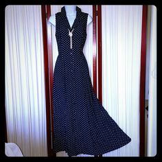 """Navy and White Polka Dot Maxi Gorgeous sleeveless, collared, button down maxi. It has a pretty full skirt that allows for beautiful draping. The buttons end about 12"""" from the bottom of the dress, allowing you to show as much leg as you desire. The bow tie in the back of the dress allows you to: a) look absolutely adorable, and b) adjust the waist cinching if necessary. NOTE: the dress is the color of the full length picture, dark navy blue. There is a slight sheen to it which reflected in…"""
